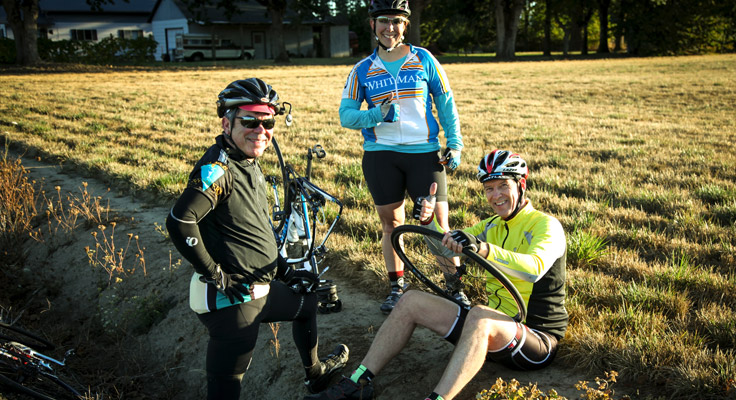 Harvest Century riders helping fix a flat tire