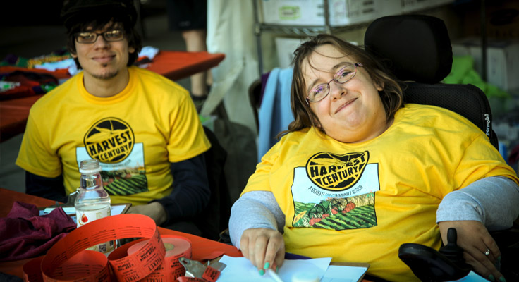 A disabled Harvest Century volunteer smiles